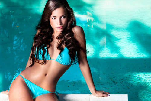Beautiful brunette woman in a blue bikini sitting in front of a pool