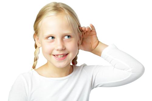 Una niña escucha con su mano en su oído