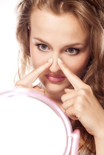 Una niña mira a su nariz en el espejo